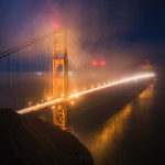 The Golden Gate Bridge at night, covered in fog and mist. Taken in San Francisco California.